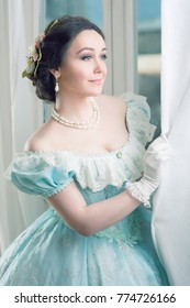 Elegant woman in historical dress waiting for friends at the ball to dance