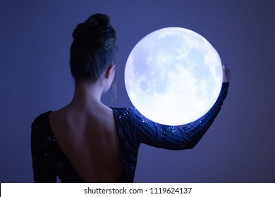 Elegant woman holding a big glowing sphere moon. Unrecognizable person, rear view