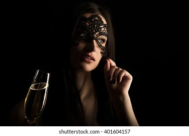elegant woman in lace mask is toasting champagne glass