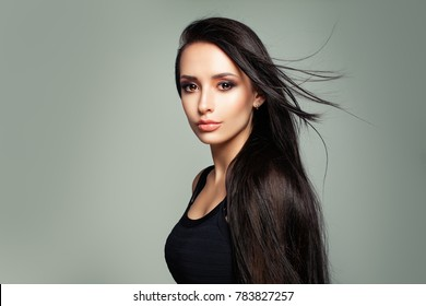 Elegant Woman with Long Hair and Makeup on Background