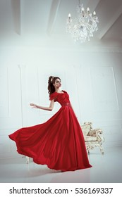 elegant woman in a long red dress is standing in a white room