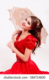 Elegant woman in a long red dress sitting on the floor and holding a vintage umbrella
