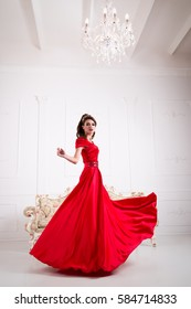 Elegant woman in a long red dress is standing in a white room chic, swirl dress