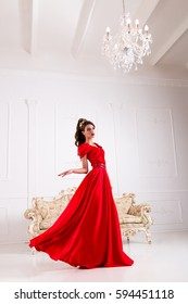 Elegant woman in a long red dress is standing in a white room, dress flashing swirl flying