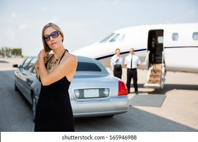 Elegant woman making hair while standing against limousine and private jet