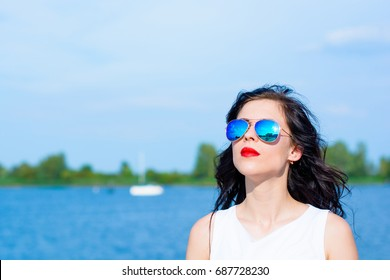 Elegant woman in mirror sunglases relax  on a embankment and thinking about something