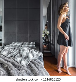 Elegant woman in modern bedroom with double bed and gray curtains