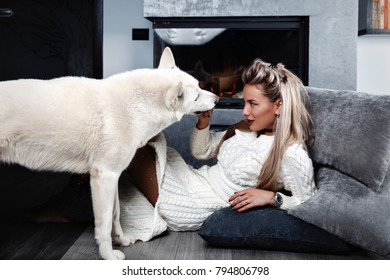 Elegant woman near the fireplace with a dog