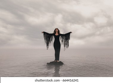 Elegant woman on water. Sunset and silhouette.