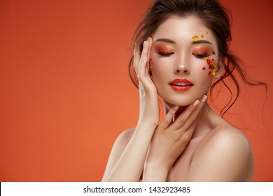 elegant woman with orange make-up anf natural flowers touching her face on orange background, sensetivy beauty copy space