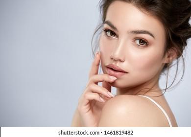 elegantes Frauenporträt mit natürlichem Make-up und goldenen Lippen auf Grau, hübsches Mädchen, das das Kinn berührt und die Kamera ansieht