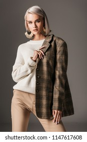 elegant woman posing in white sweater and autumn tweed jacket, on grey