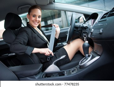 elegant woman putting on safety belt in her car