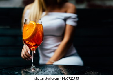 Elegant woman ready to drink aperol spritz cocktail. Summer cocktail in restaurant