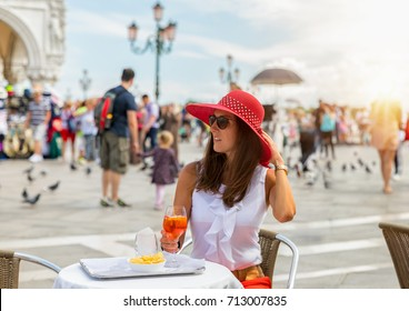 Elegant woman with a red hat enjoys an Aperitif on the famous St. Mark's Square in Venice, Italy