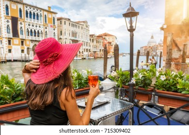 Elegant woman with a red hat enjoys an aperitif sitting next to the Canale Grande in Venice, Italy
