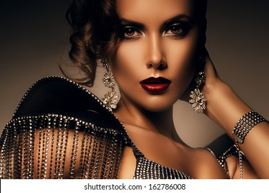 elegant woman with red lips in accessories of stones