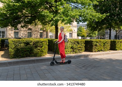 Elegant woman rides e-scooter in the city