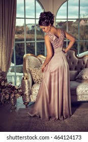 elegant woman in a rose colored evening dress