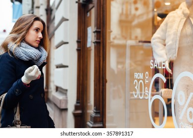 Elegant woman with scarf and winter gloves looking at boutique showcase