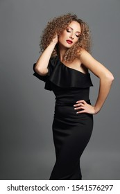 Elegant woman sexy dress with wavy hairstyle posing, on a gray studio background. Beautiful blonde model wearing a black dress, red lips, curls, party. Fashion style holiday.Hairstyle wavy hair