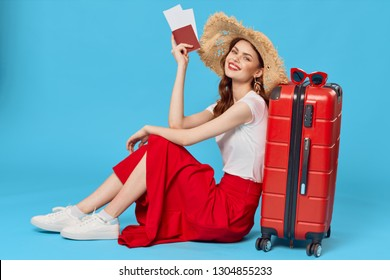 Elegant woman sitting on the floor, leaning on a red suitcase with a passport in her hands and travel tickets