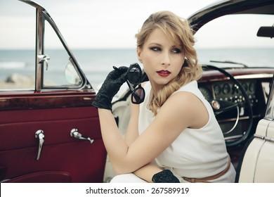 Elegant woman sitting in vintage car