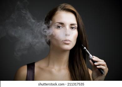 Elegant woman smoking e-cigarette with smoke portrait