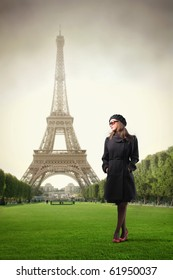 Elegant woman standing in a park with Eiffel Tower on the background