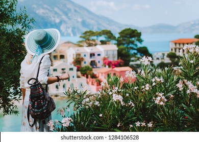 Elegant woman with straw hat and white clothes enjoying view of colorful village Assos on sunny day. Stylish female visiting Kefalonia in summer time on Greece travel vacation