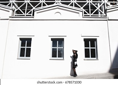 Elegant woman in the style of coco chanel near a white building with windows
