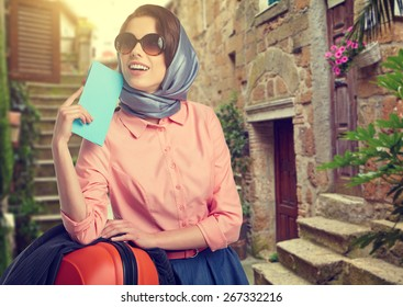 Elegant woman with a suitcase travel and ticket on street of italian city