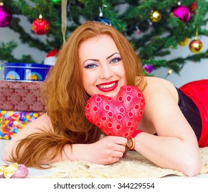 elegant woman   is under the Christmas tree with red heart at room