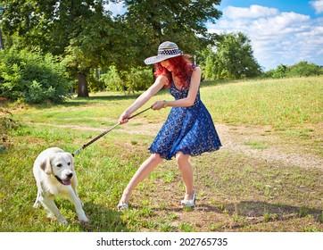Elegant woman walking her big dog in the park,  Serbia.