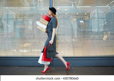 Elegant woman walking in the mall with bags and boxes