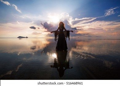 Elegant woman walking on water. Sunset and silhouette.