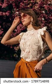 Elegant woman wearing big trendy sunglasses, earrings, golden wrist watch, lace blouse, posing in street. Outdoor fashion portrait