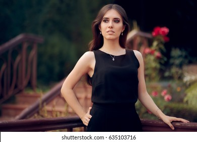 Elegant Woman Wearing Black Dress Standing in a Patio - Portrait of a chic girl in all black dress code outfit