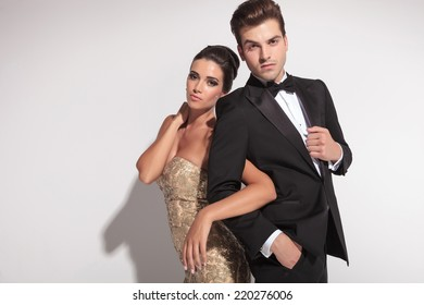 Elegant woman wearing a golden dress holding her man by arm and both posing in studio.