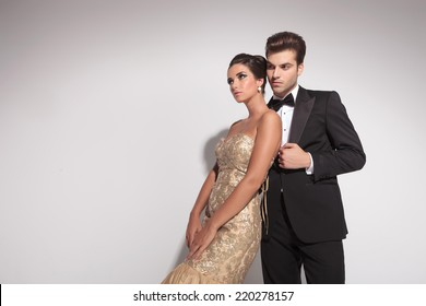 Elegant woman wearing a golden dress leaning on her lover, both looking away. On grey studion background.