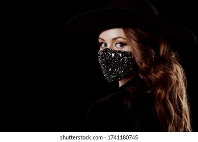 Elegant woman wearing luxury fashion outfit during quarantine of coronavirus outbreak. Black suit including stylish luxury face safety mask with rhinestones. Close up portrait. Copy, empty space