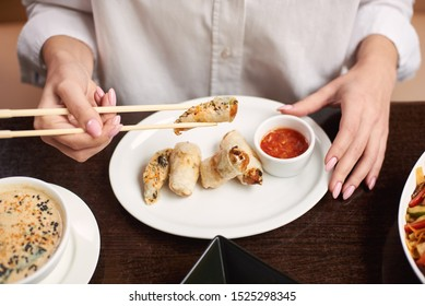 Elegant woman in white blouse enjoying dinner in restaurant. Female well groomed hands with manicure holding tempura shrimp with food sticks. Three course lunch from soup, tempura dish and vegetables.