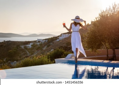 Elegant woman in white dress enjoys an aperitif by the swimming pool during sunset time in summer