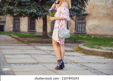 Elegant woman's legs in dark leather roman sandals. Blonde woman in light pink summer dress with light blue handbag in the city. Street fashion outfit.