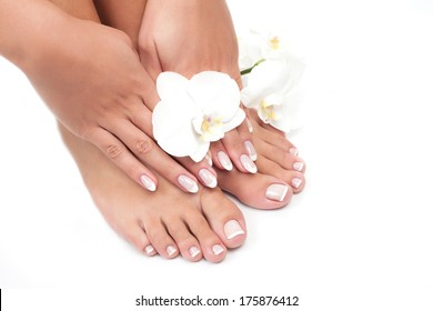 Elegant woman's manicured hand and pedicured feet with orchid flower