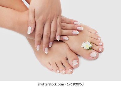 Elegant woman's manicured hand and pedicured feet with flower