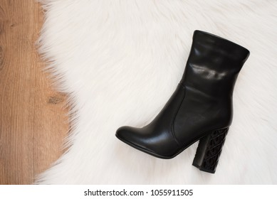 Elegant women black high heeled boots. Top view of black boots on a white fur carpet, wooden background. Concept of fashion and design, shopping
