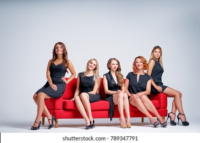 Elegant women. Group portrait of five attractive caucasian models wearing black dresses sitting on the red sofa.