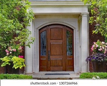 elegant wooden front door and portico entrance surrounded by flowers of upper class house