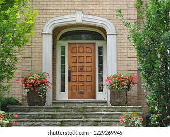 elegant wooden front door with sidelights and transom window, on brick house with stone steps